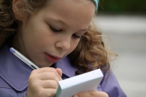 Garotinha concentrada escrevendo